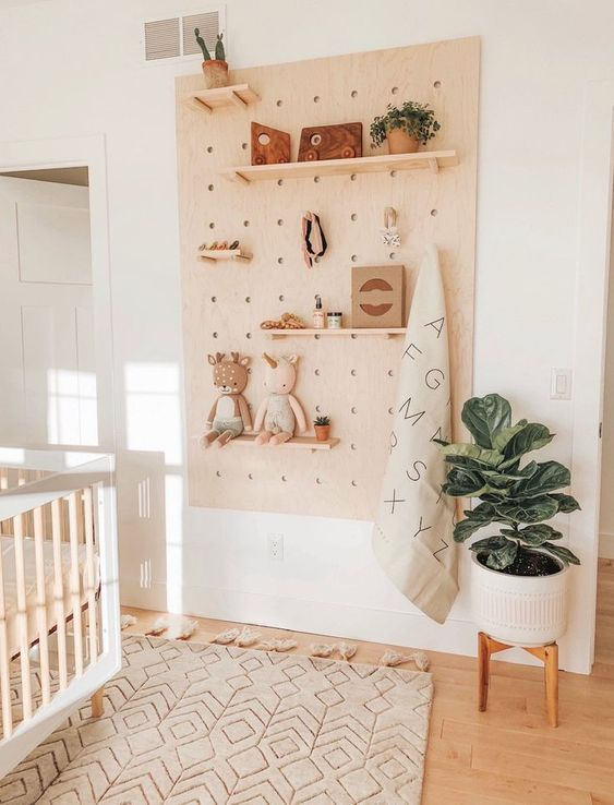 wooden pegboard in the nursery with decor items