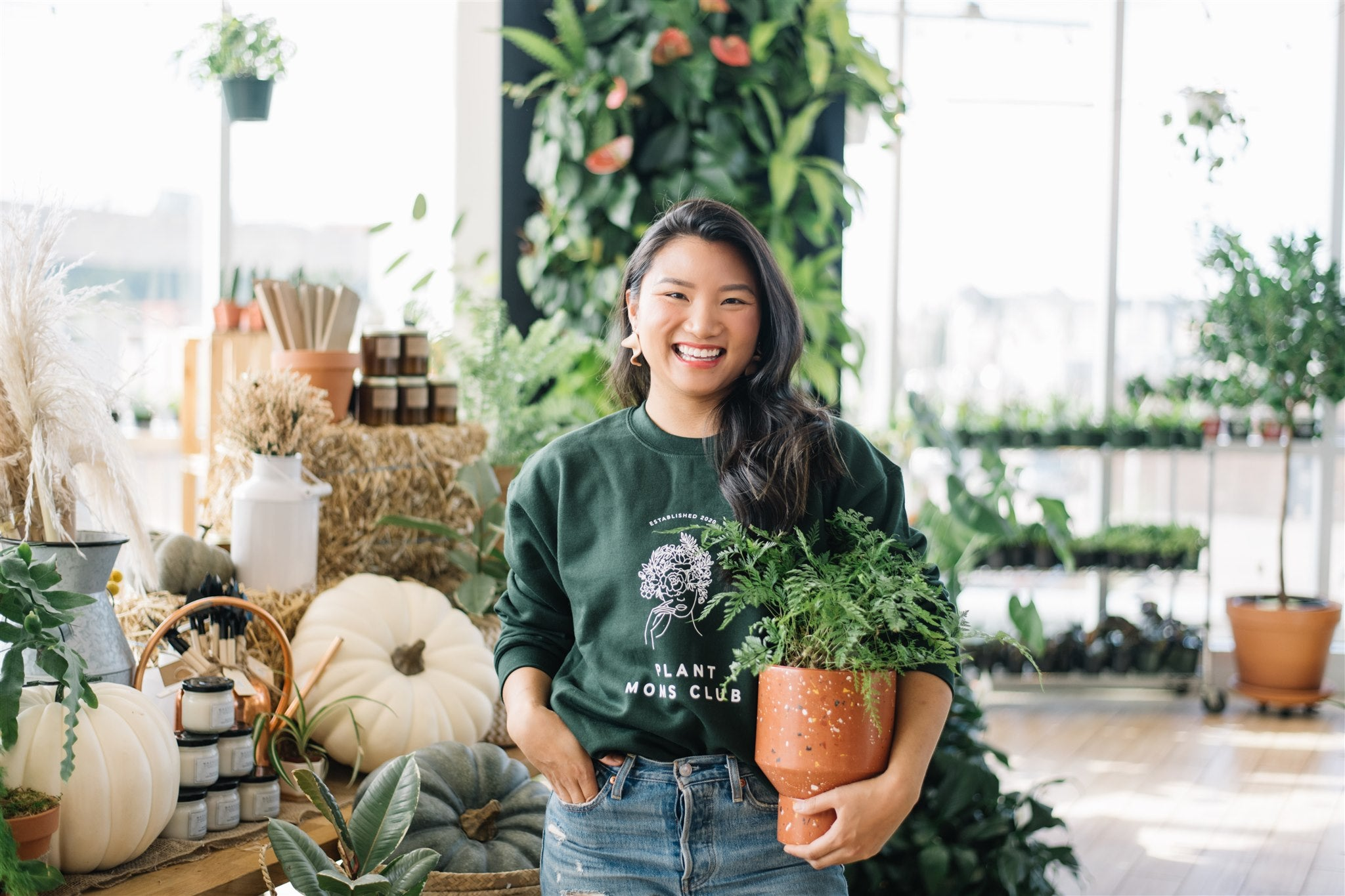 Woman wearing a plant moms club green crewneck sweater with terrazzo planter and a plant shop