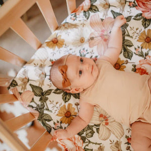 baby girl in crib with white floral crib sheet
