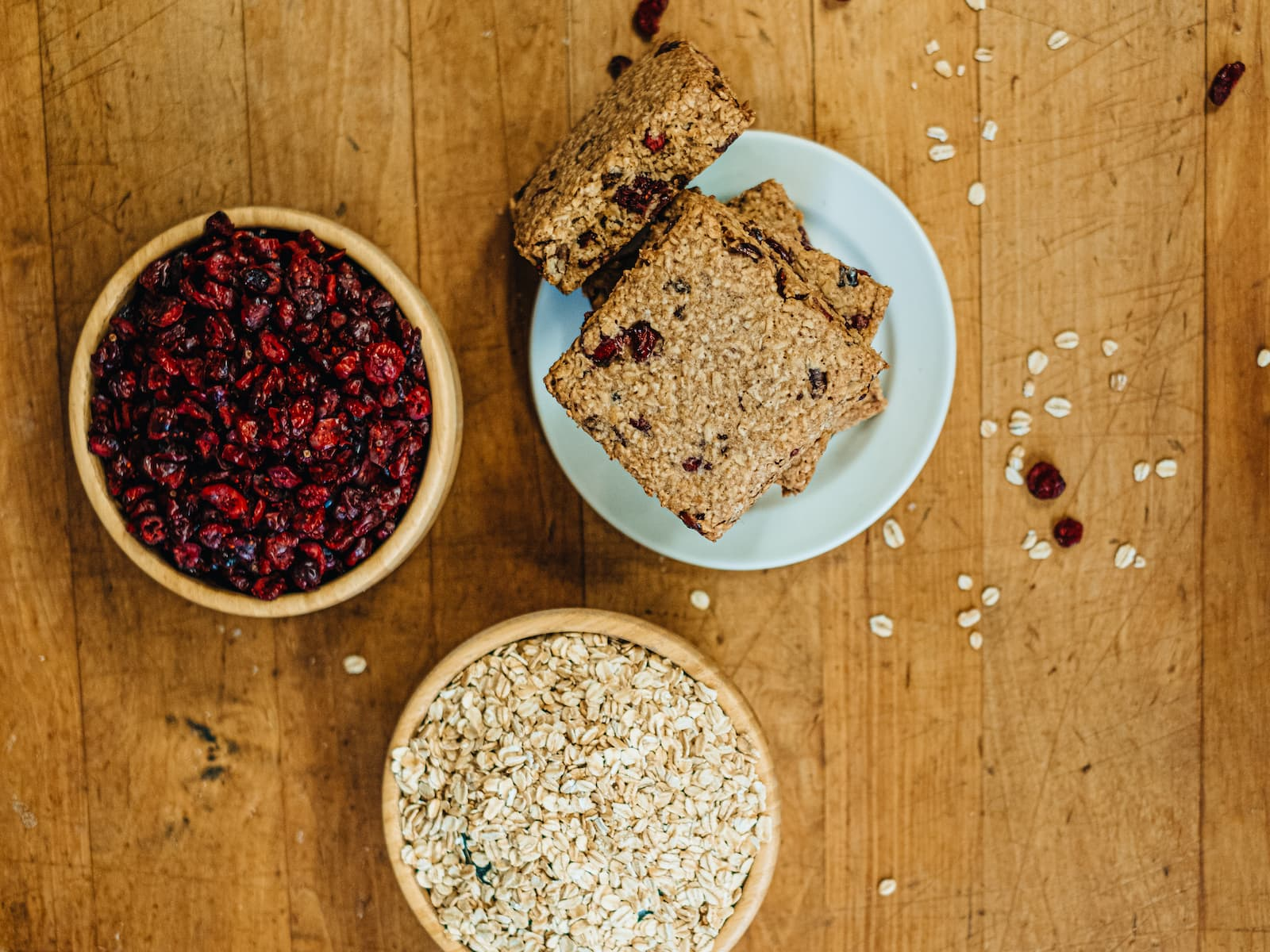 Oatcakes on a table next to cranberries and oatmeal