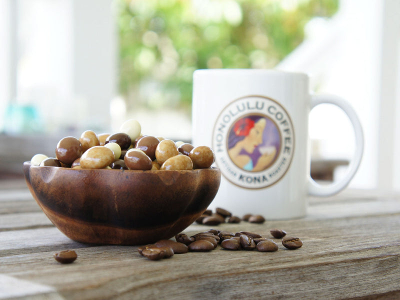 Mixed chocolate covered coffee beans sitting in a bowl next to a Honolulu Coffee Mug
