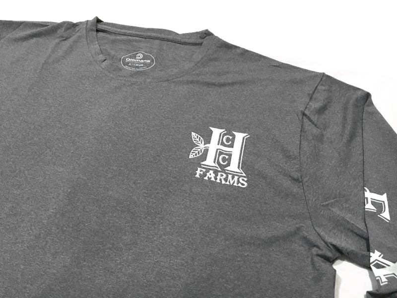 "A close up of the chest of the Grey long sleeve farm shirt from Honolulu Coffee - ""Coffee Farms"" down the sleeves"