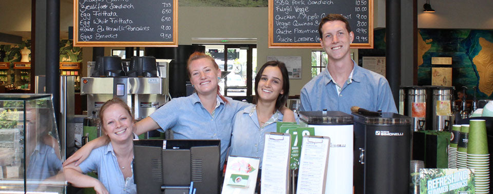 Honolulu Coffee Baristas smiling behind the bar inside one of our Honolulu Hawaii cafes