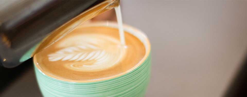 Pouring latte art in a cappuccino cup filled with Kona coffee espresso