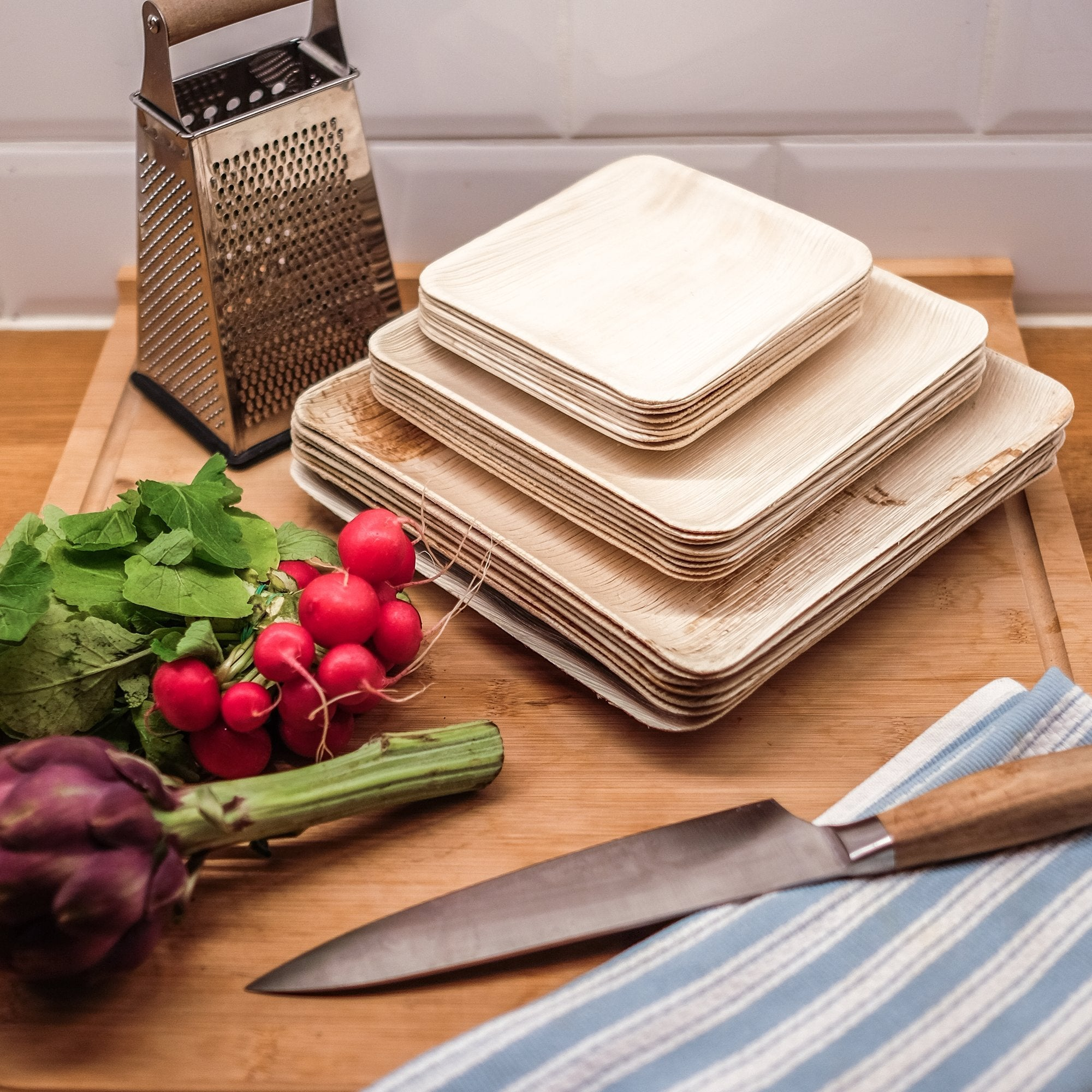 square leaf plates in varying sizes displayed with kitchen tools and ingredients