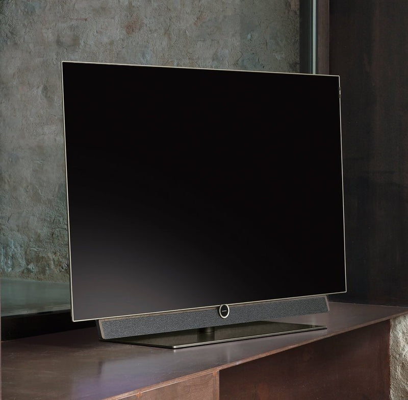 "Loewe bild 5 55"" OLED TV with Silver Oak Floor Stand on the table"