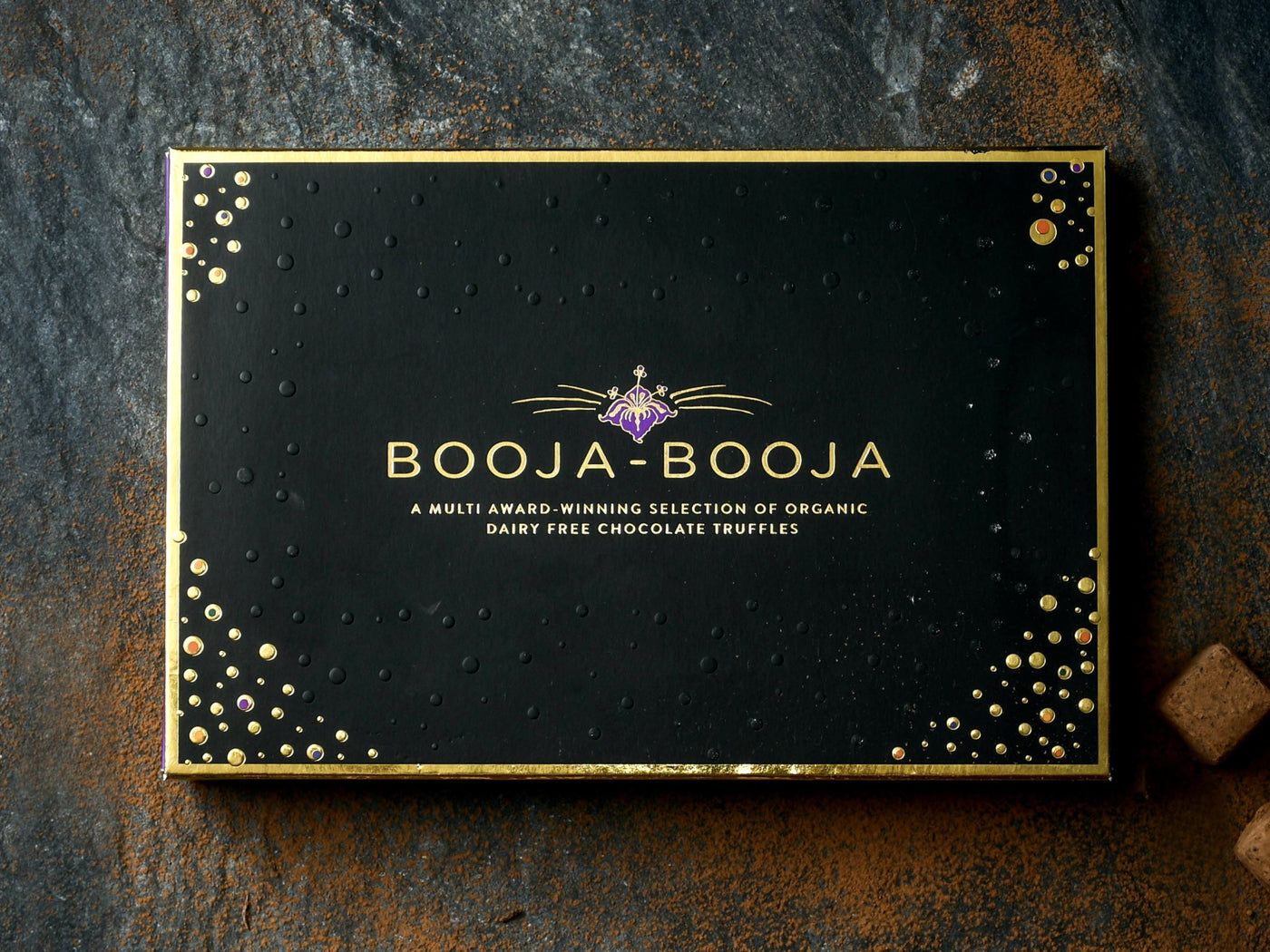 The Booja-Booja Award Winning selection of vegan and organic chocolate truffles, photographed on a slate background with individual chocolate truffles