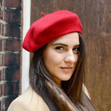 Model in red wool beret with camel coat