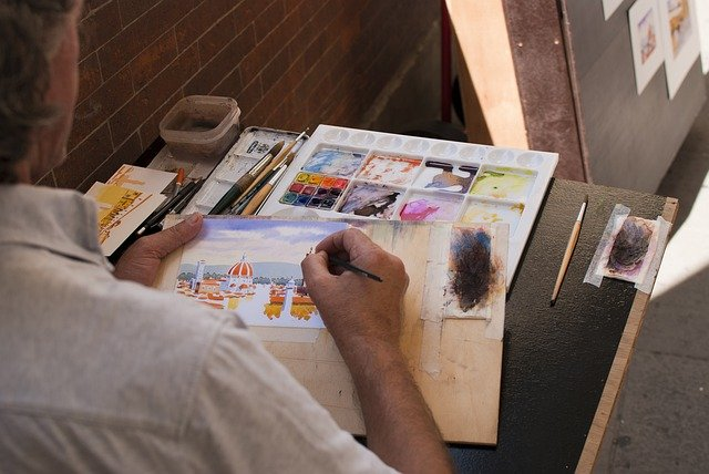 Adult man painting a scenery