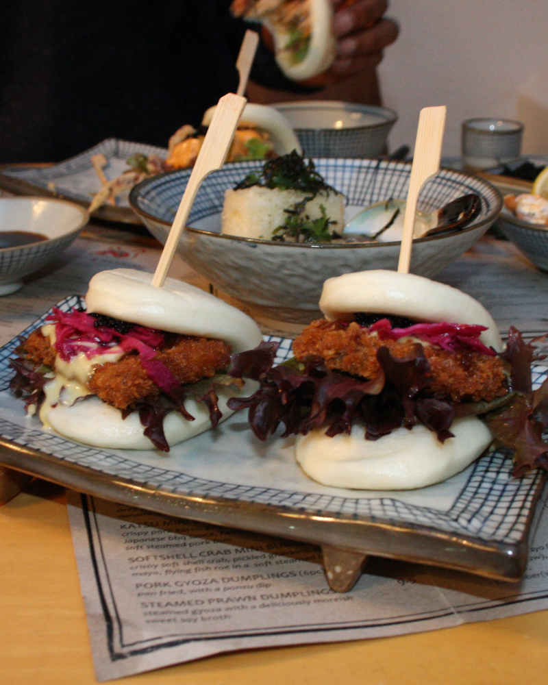 Two steamed baos sliced in half, filled with crispy golden pork katsu, pickled red cabbage, lettuce, flying fish roe & kewpie mayo, held together with wooden stick.