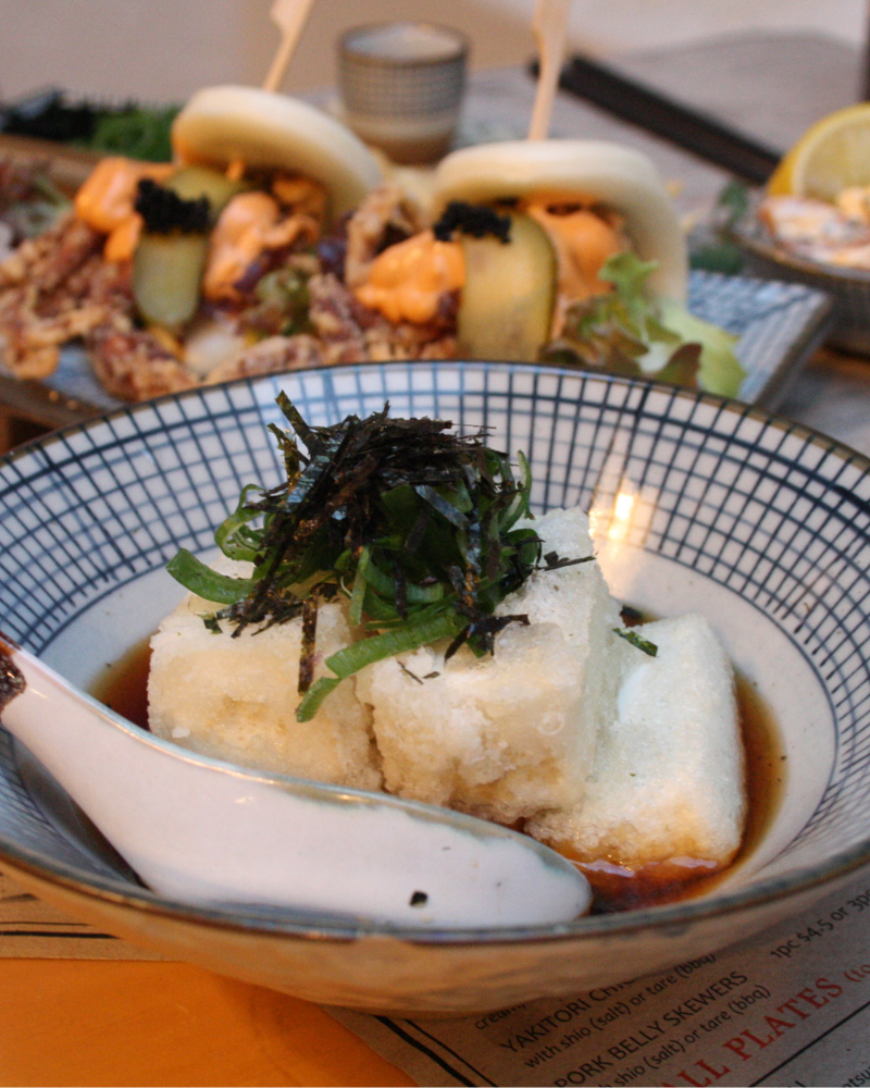 Bowl of golden fried tofu pieces sitting in tentsuyu sauce, topped with sliced shallots and shredded nori (seaweed)