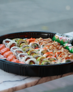 Sushi Platter with various sushi rolls in a black round platter