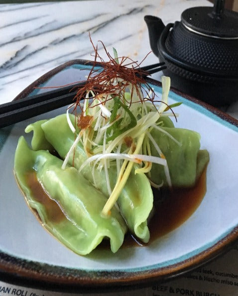 Green coloured steamed vegetable dumplings in sweet soy broth, topped with sliced leeks