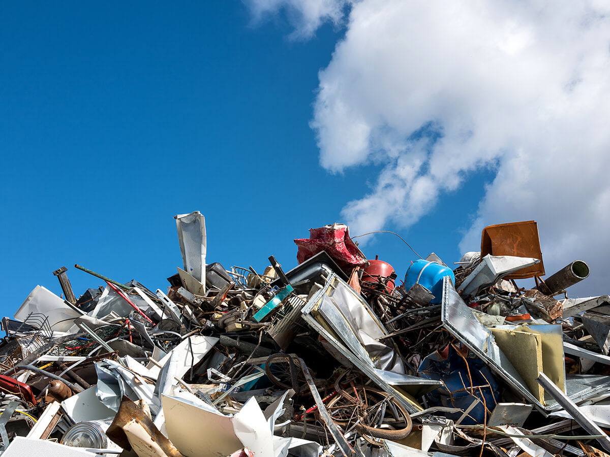Pile of trash at landfill with blue sky in the background.