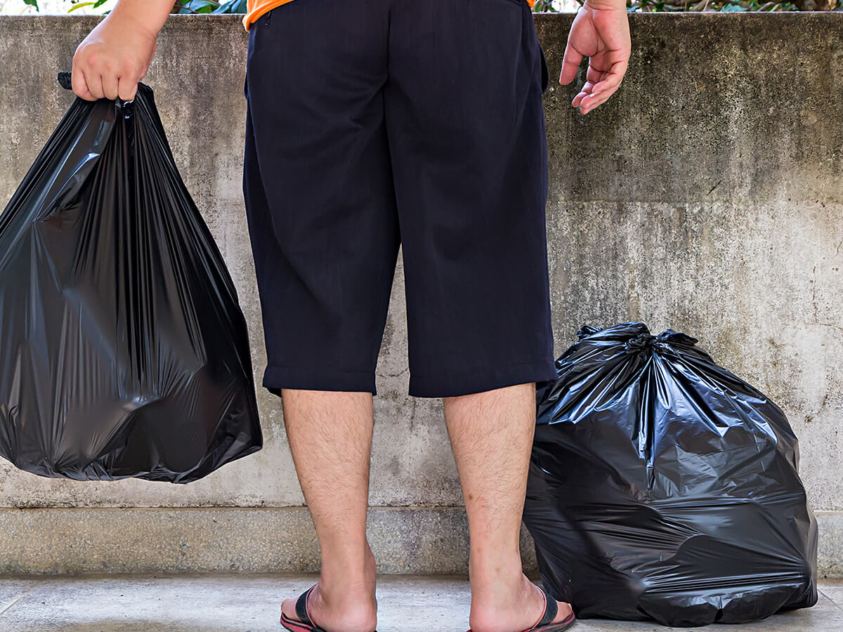 Man holding a trash bag with another trash bag on the ground by his feet.