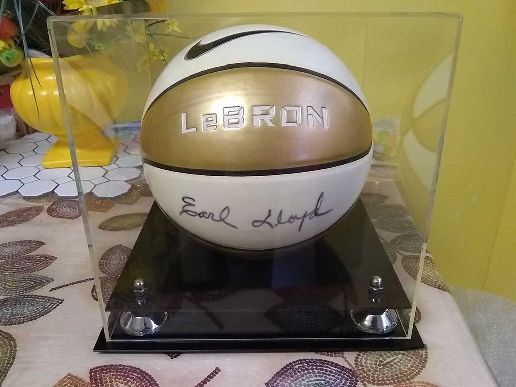 Pictures of a basketball signed by Earl Lloyd in one of our display cases