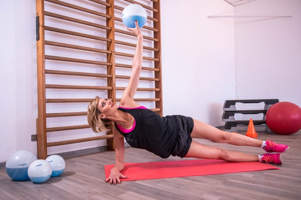 woman working out with SPHERA2.0 exercise ball in her home gym