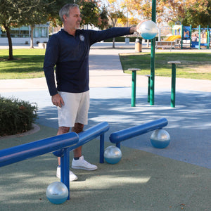 man exercising outside with a set up weighted Sphera2.0 therapy medicine balls