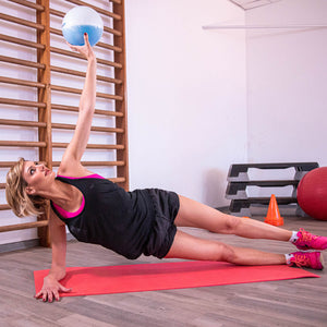 woman doing side plank exercises with weighted Sphera2.0 medicine ball in a home gym