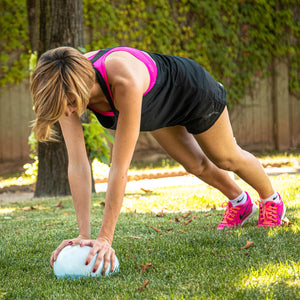 woman exercising outside planking with a Sphera2.0 therapy medicine ball
