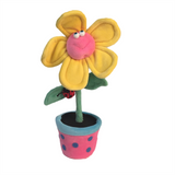Plush yellow and pink smiling flower in a pink pot with blue polka dots soft sculpture