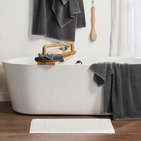 Freestanding tub with Lotus towels in charcoal shown draped over tub and hanging above it. A white Lotus bath mat is next to the tub in a luxurious bathroom setting.