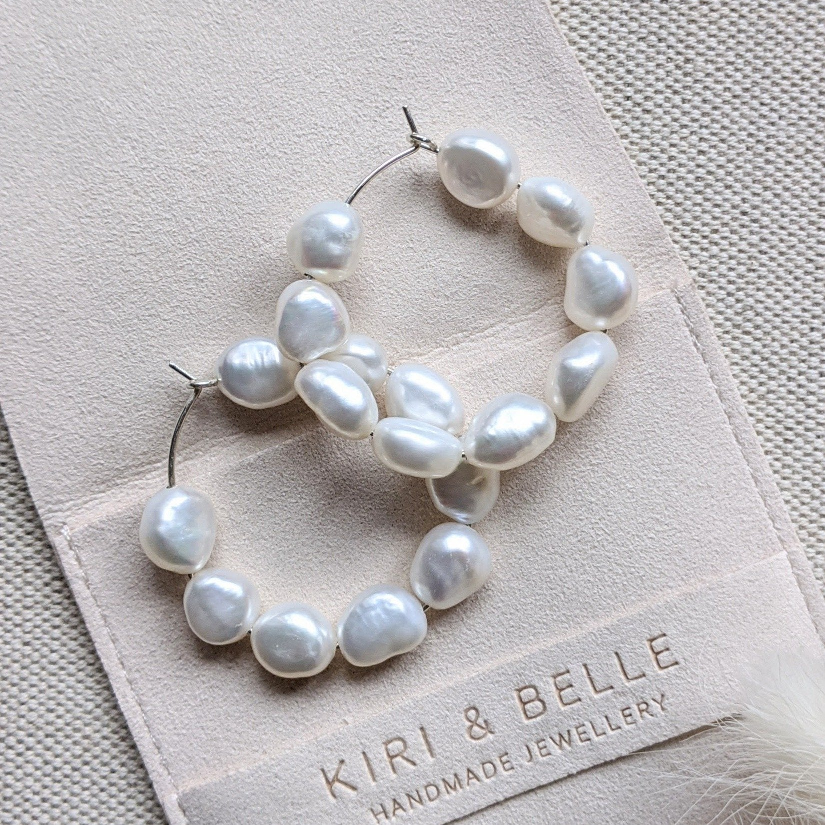 Kiara hoop earrings with 9 9mm baroque freshwater pearls on faux suede pouch