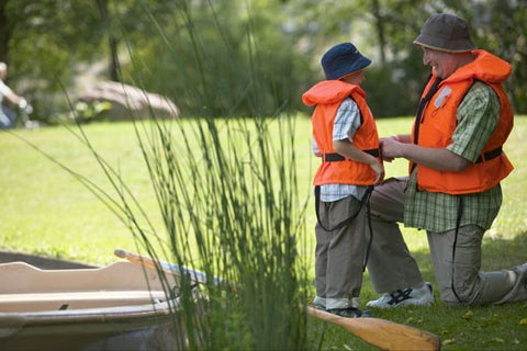 boy wearing life jacket with father