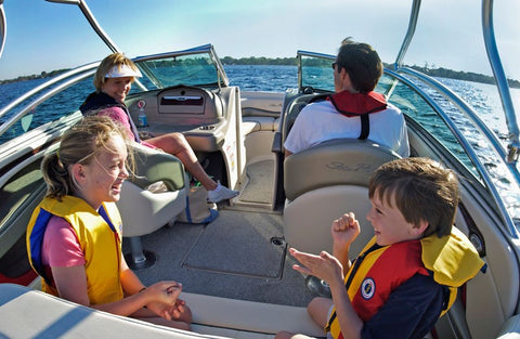 family wearing life jacket on a boat