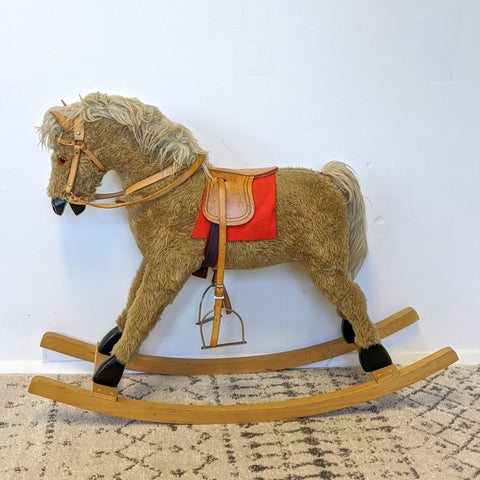 Golden rocking horse with leather saddle and bridle