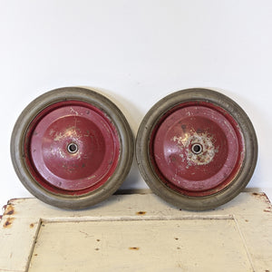 Two, red pedal car wheels with grey rubber tires