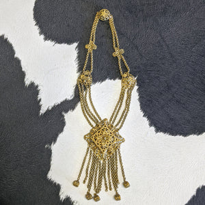 Gold Victorian necklace with flower detailing that meet with a diamond shaped center and fringe.