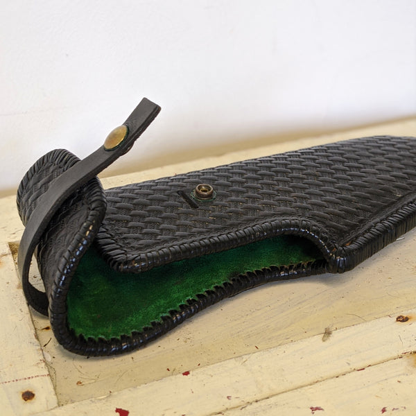 Leather gun holster unsnapped with green fabric inside