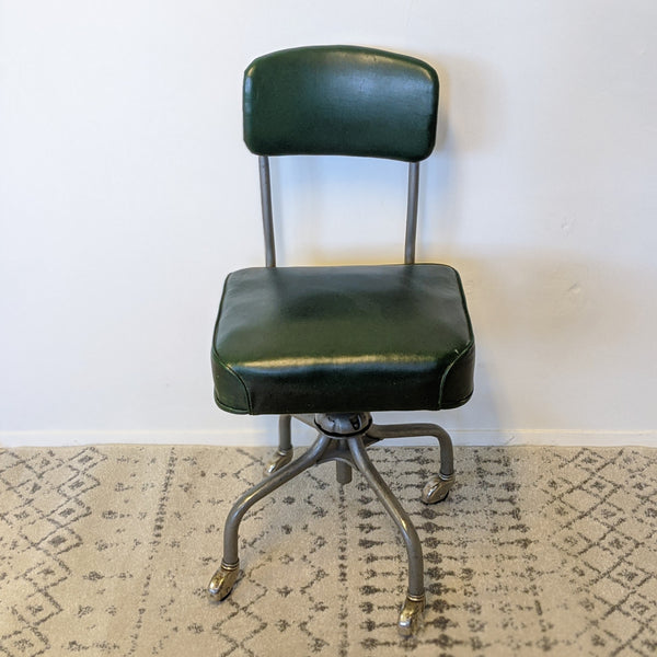 Green and metal industrial chair with wheels