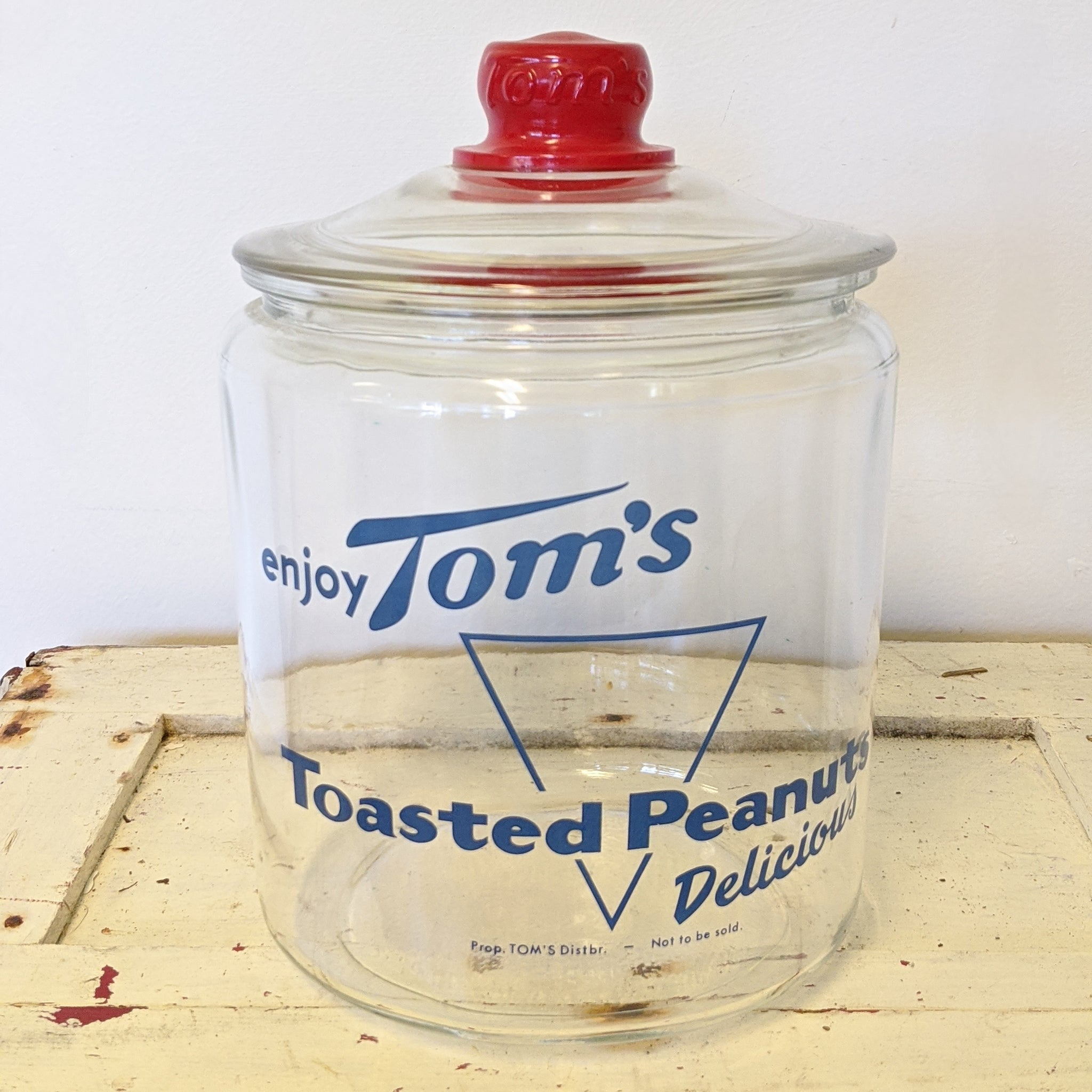 Wide, clear jar with blue lettering and red lid handle