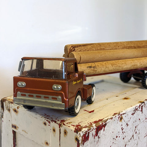 Dark red toy log truck with logs