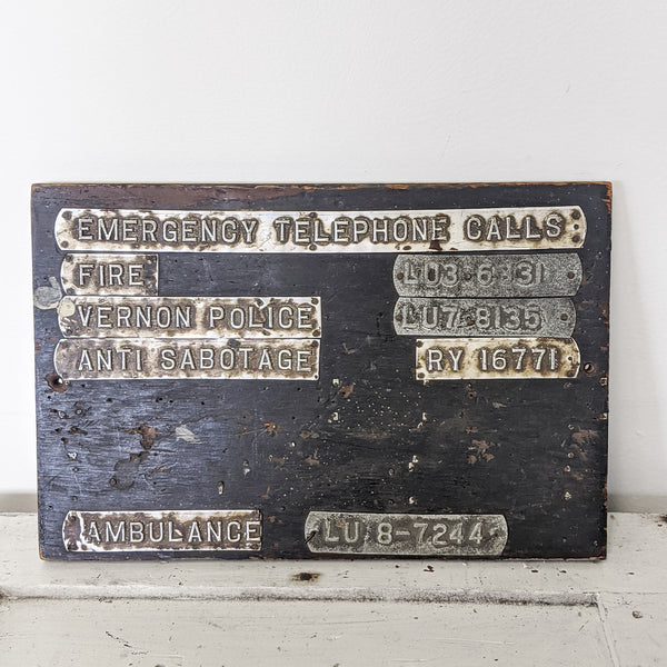 Black vintage emergency telephone calls sign with metal plaques