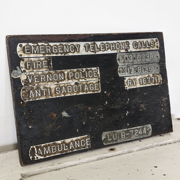 Black vintage emergency telephone calls sign with metal plaques close up