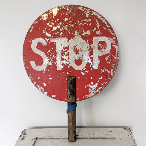 Red metal stop sign with wooden handle and white letters