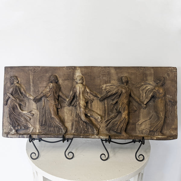 Long rectangular sculpture of Grecian goddesses holding hands. Placed on two black stands