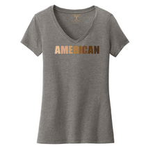 "Load image into Gallery viewer, Heather grey women's v-neck cotton/poly short sleeve graphic t-shirt with ""American"" printed in a gradient of skin tones."