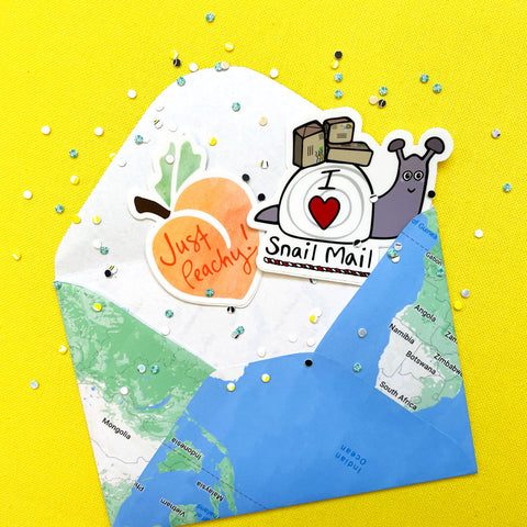 Yellow background with a handmade green and blue paper envelope made from a repurposed map with multicolored confetti and 2 vinyl stickers: 1 Just Peachy orange fruit sticker and 1 Snail Mail purple snail sticker by Sunny Day Designs - Snail Mail Fun Blog Post