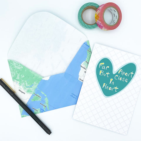 Blue and Green Mailing Envelope Made From a Repurposed Map next to Colorful Washi Tape, a pen, and a Far Apart Heart greeting card by Sunny Day Designs - Snail Mail Blog Post