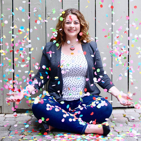 Sunny Day Designs Designer, Shelley Schmidt - Seated Outside, Smiling, and Throwing Colorful Confetti Into The Air
