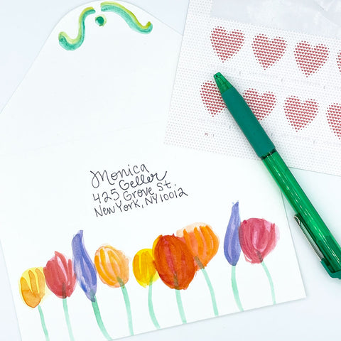 Colorful Watercolor Painted Floral Envelope with Heart Postage Stamps and Green Pen. Painted by Sunny Day Designs - Snail Mail Fun Blog Post