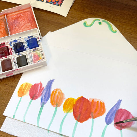 Colorful Watercolor Flowers Painted onto White Envelope Next to Watercolor Paint Set and on Wood Table. By Sunny Day Designs - Snail Mail Fun Blog Post