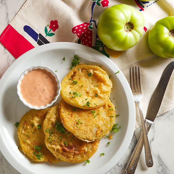 Friend Green Tomatoes with a dipping sauce and fresh green tomatoes