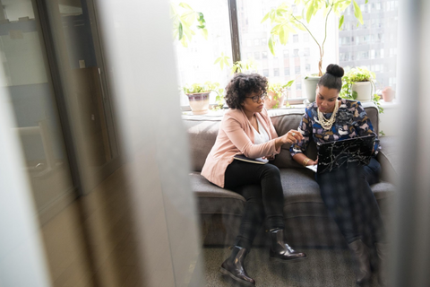 Two black business woman talking while sitting in a couch