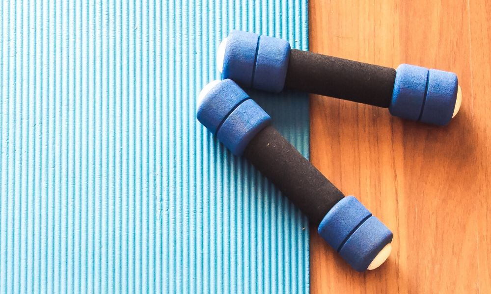 A yoga mat and two weights on a hardwood floor.