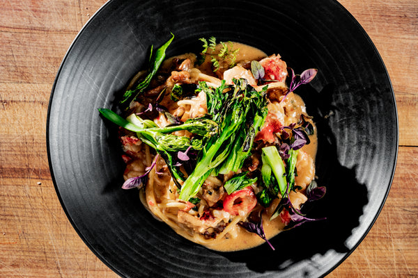 lobster dish with broccolini on black plate